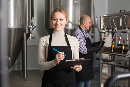 production facility: Portrait of happy woman employee in modern beer production facility
