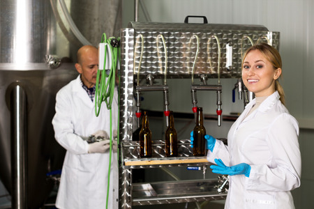 bottling: Portrait of young positive female brewery worker with bottling machinery on factory
