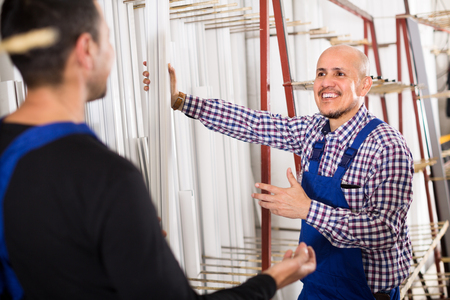 toolroom: Two positive workmen in blue coverall in workshop of PVC windows and doors