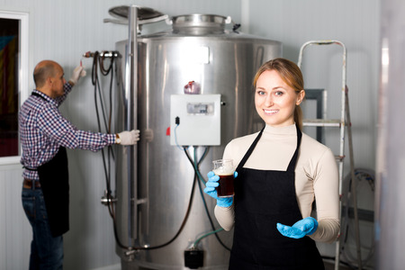 fermenting: Young pretty woman wearing uniform standing among brewery stainless equipment Stock Photo