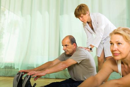 personal medico: El personal m�dico en el gimnasio de ayudar a los pensionistas pareja para tomar posici�n correcta. Centrarse en el hombre Foto de archivo