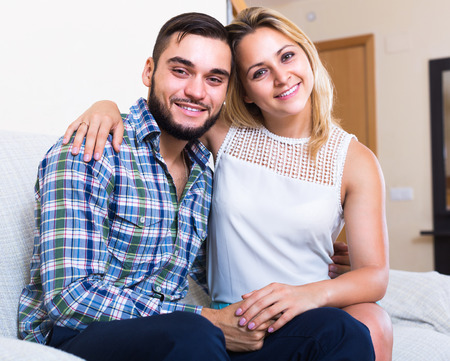 couple on couch: Portrait of happy young smiling couple sitting on couch Stock Photo