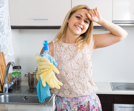 tidying up: Portrait of cheerful young blonde girl tidying up at home kitchen