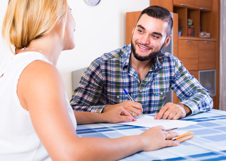 Smiling young couple at the table  filling forms for joint banking account