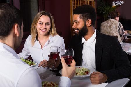 middle class: Feliz sonriente joven pareja de clase media y amigo disfrutando de la comida en el café