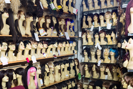 peruke: Mannequins with variegated style wigs on shelves of hair salon Stock Photo