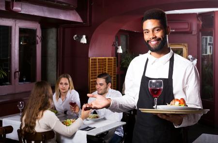 clase media: Retrato de las personas adultas en el restaurante de clase media y el camarero negro positivo Foto de archivo