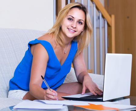 yuppie: Happy russian female student studying with laptop and notes indoors