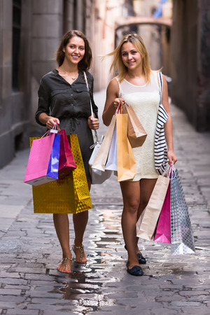 spendthrift: Two cheerful girls with shopping bags in hands walking by street Stock Photo