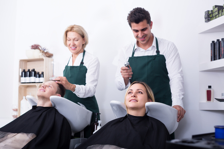 19's: Two smiling hairdressers working with hair of clients in washing tray. Selective focus