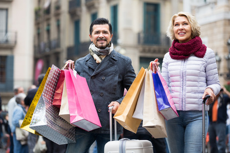 shopping trip: Happy mature couple of travellers enjoying shopping trip during voyage Stock Photo