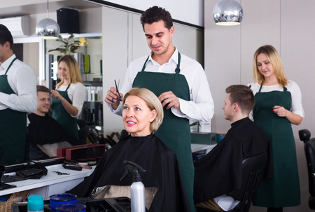hairdressing saloon: Smiling dark-haired man doing hairstyle for mature woman in hairdressing saloon. Selective focus on woman Stock Photo