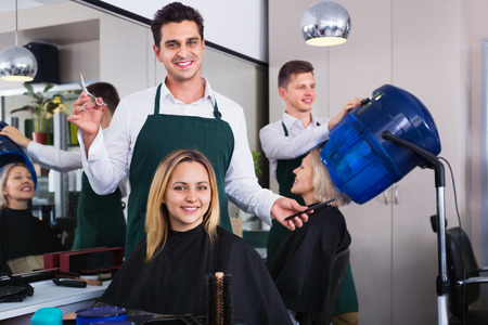 hairdressing saloon: Cheerful smiling man cutting long hair of girl in hairdressing saloon Stock Photo