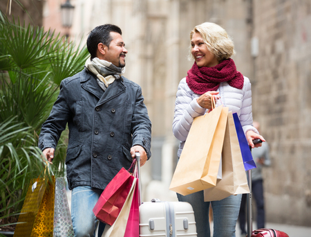 60's: Happy mature couple of travellers 60s enjoying shopping tour during voyage Stock Photo