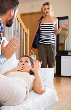 homosexual partners: Jealous guest catching scared partner with lover indoor Stock Photo