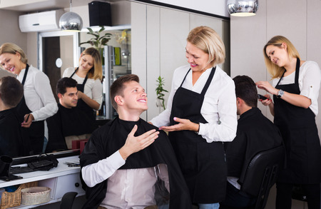 peignoir: Happy elderly hairdresser serving teenager guy in chair
