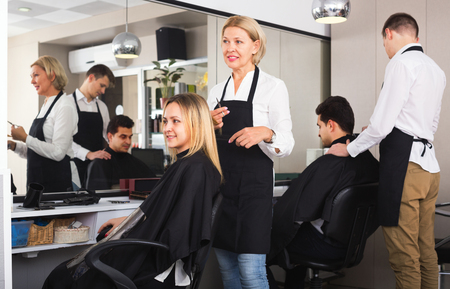 peignoir: Cheerful aged woman cutting girl hair in the barbershop Stock Photo