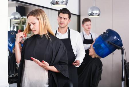 Beautiful upset woman blaming hairdresser in bad haircut Stock Photo