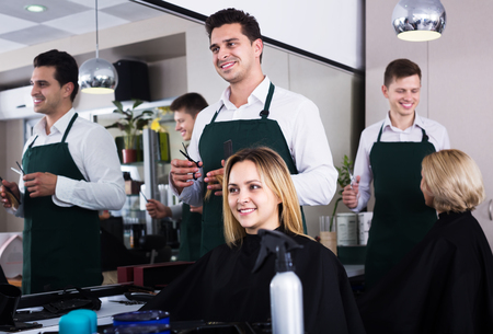 18's: Positive hairdresser cuts hair of blonde girl in barbershop Stock Photo