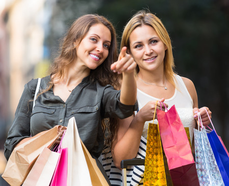 spendthrift: Portrait of two beautiful girls with shopping bags at street Stock Photo