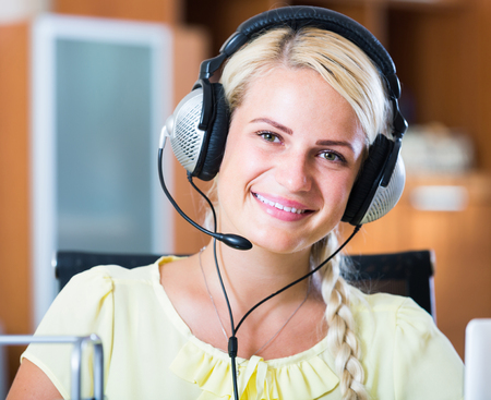 yuppie: Adult girl answering the call of technical support and smiling