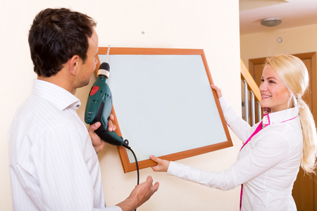 wall decoration: Young couple drilling Wall to Hang picture frame Stock Photo