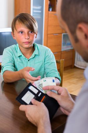 money pocket: padre pidiendo ordinaria muchacho adolescente por poco dinero de bolsillo en casa