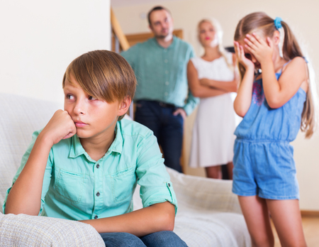abusing: Little sister and brother abusing each other, a parents standing near them at the home