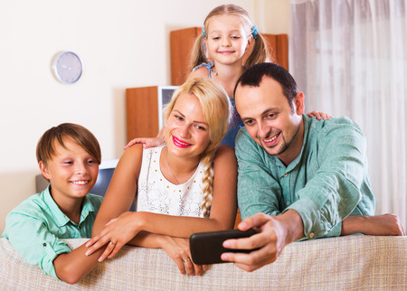 clase media: Portrait of happy middle class family with two children at home interior. Focus on woman Foto de archivo