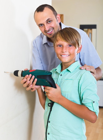 modifying: Positive man teaching son to using electric drill wall at home
