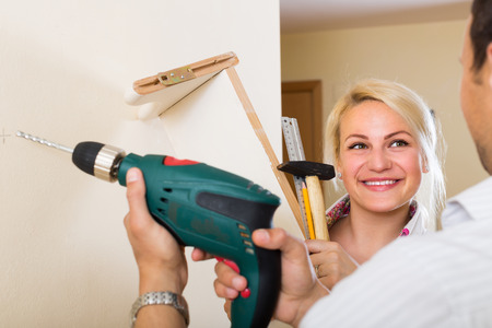 modifying: Positive young married couple makes repairs at home