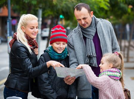 middle class: Feliz familia de clase media de cuatro comprobación dirección en el mapa