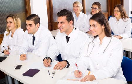 faculty: Happy multinational interns and professor having discussion at medical faculty