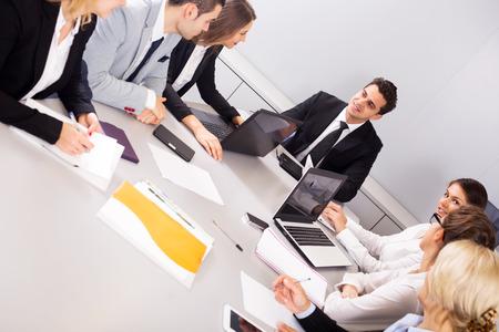 reuniones empresariales: miembros de negocios felices de las reuniones multinacionales en la oficina. Centrarse en el hombre y la mujer derecha