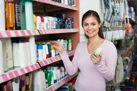 glad: Glad female customer selecting antiperspirant in drugstore Stock Photo