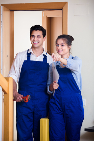 tooling: handyman and female assistant in uniform with tooling