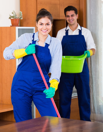 cleanup: Cheerful smiling professional cleaners doing cleanup in ordinary apartment
