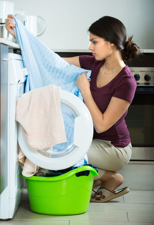 loathsome: Unhappy young  brunette woman with dirty curtains near washing machine