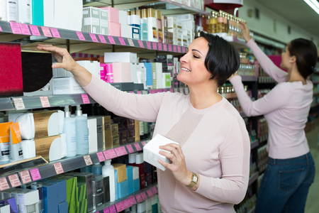 gay girl: Gay young girl and mature woman choosing cream in beauty department