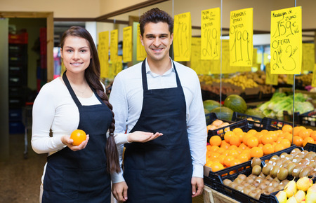 25s: Positive young sellers offering good price for fruits in grocery Stock Photo