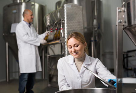 production facility: Portrait of glad young woman employee in modern beer production facility Stock Photo