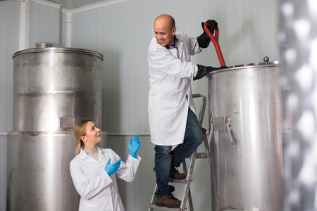 production facility: Joyful man and woman in white coats working on modern beer production facility