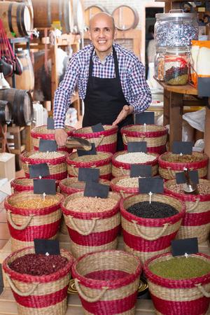 diligente: vendedor de sexo masculino que muestra diligente frijoles secos en el bazar