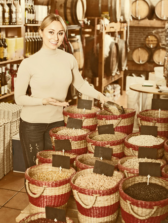 selecting: Smiling female customer selecting dried beans in shop Stock Photo
