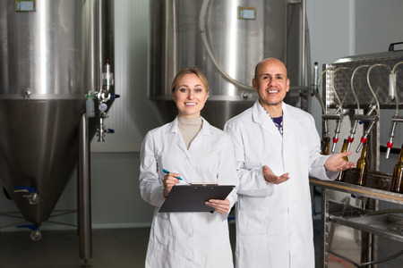 production facility: Cheerful smiling man and woman in white coats working on modern beer production facility. Focus on woman Stock Photo
