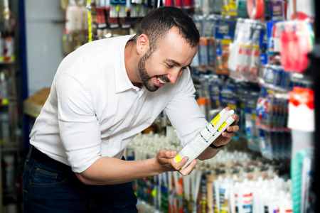 hermetic: Young cheerful man choosing sealant tube in household store Stock Photo