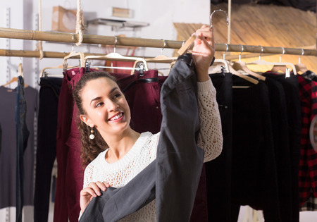 breeches: Smiling  brunette girl selecting new breeches at the store Stock Photo