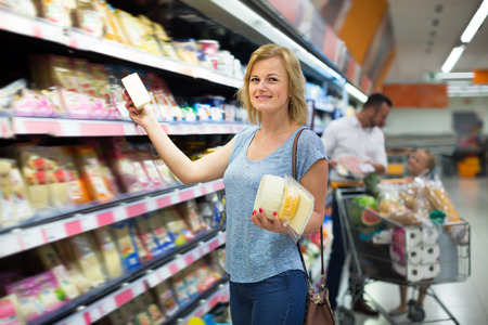 selecting: Young female customer selecting cheese in refrigerated section in hypermarket Stock Photo