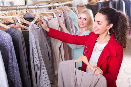 garments: Two smiling young women choosing basic garments at clothing store