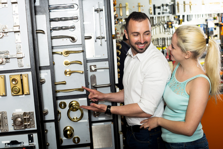 lintel: Smiling man and woman picking door lintel and handle together in household shop